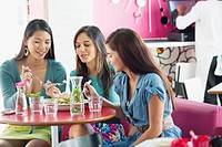 Three women eating food in a restaurant