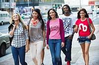 Friends walking on the sidewalk against cars