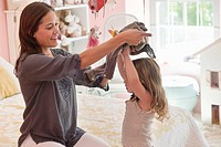 Happy woman dressing her daughter at home