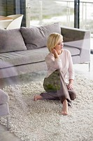 Young woman sitting on a rug and thinking