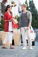 Young couple looking at each other with shopping bags on a street