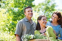 Woman standing with his son and daughter in law while holding basket of flowers