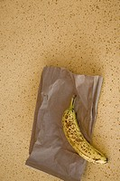 Ripe banana and lunch bag on a table