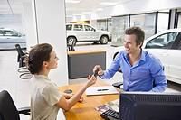 Saleswoman handling car key to a man