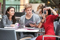 Three young friends sitting in a restaurant with one woman using camera