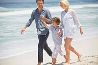 Couple with their son walking on the beach
