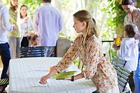 Little girl cleaning dining table after eating food with family in the background