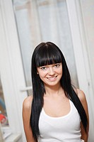 pretty brunette girl indoors with window on background