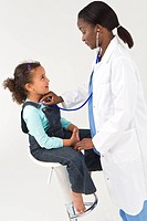 African American Female Doctor Examining Interracial Girl Child