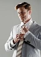 portrait of young businessman adjusting his tie