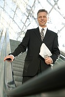 businessman standing on escalator