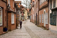 Old man walking down a cobbled street in Lu¨neburg old town Lower Saxony, Germany