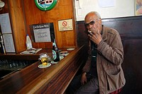 Rotterdam, Netherlands. Senior adult male drinking a beer while sitting at a bar down town Nieuwe Binnenweg.