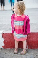 Toddler girl standing on sidewalk, looking over her shoulder