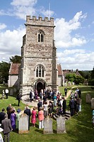 wedding guests and family watching bride and groom outside St Mary & Cuthberga & All Saints Church Witchampton