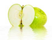 beautiful juicy green apple with water drops on the water isolated over white