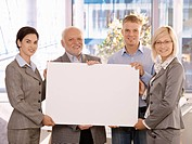 Business team holding blank poster for copy space