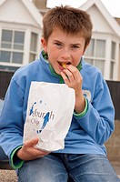 An eleven year old boy eats fish & chips on the sea wall in Aldeburgh , Suffolk , England , Britain , Uk