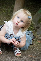 A one-year-old caucasian girl outdoors.