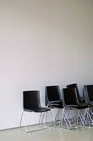 Stacked black chairs in front of a white wall