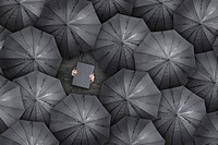 Person with briefcase over head standing between black umbrellas, directly above