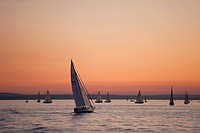 Germany, Lake Constance, Boat sailing on lake at dusk