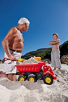 Man playing with grandson on beach