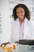 Smiling pharmacist working with medication