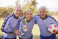 Senior Chilean soccer players holding trophy and soccer ball