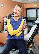 Older woman drinking water in gym