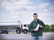 Trucker holding goat´s milk by tanker