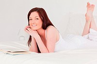 Attractive red_haired woman reading a book while lying on her bed