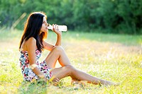 Attractive young woman with a bottle of water on the grass