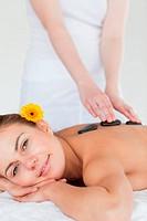 Portrait of a woman enjoying a hot stone massage in a spa