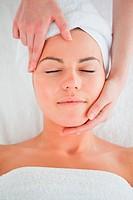 Portrait of a woman enjoying a facial massage in a spa
