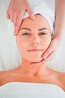 Portrait of a cute woman enjoying a facial massage looking at the camera