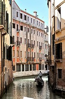 Vertical image of a canal with a gondola sailing by in Venice, Italy