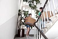 Germany, Cologne, Young couple carrying carton on stairway in renovating apartment
