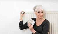 Germany, Duesseldorf, Woman holding banknotes and adjusting heater at home, smiling, portrait