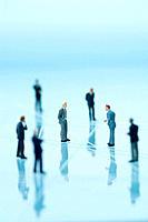 Businessmen figurines standing on blue background