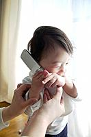 Mother Helping Baby Girl with Mobile Phone