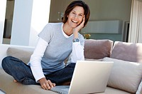 Portrait of a mature woman sitting on a couch and smiling