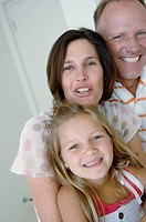 Close_up of a mid adult couple with their daughter smiling