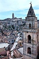 Aerial view of ancient town of Matera with tufa houses, bell tower of church in foreground, and Duomo on hill beyond, sunny spring morning with blue s...