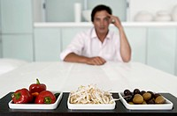 Close_up of a tray of food on the dining table with a young man sitting in the background