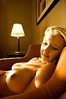 Caucasian young adult nude woman reclining and smiling.