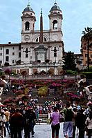 Spanish steps, with church of Trinita dei Monti above, tourists on sunny summer day, and flowers on steps, Rome