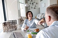 Mature woman feeding her husband and smiling