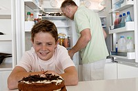 Close_up of a boy looking at a cake with his father standing behind him in front of an open refrigerator