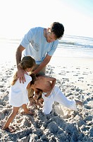 Mid adult man with his children playing on the beach